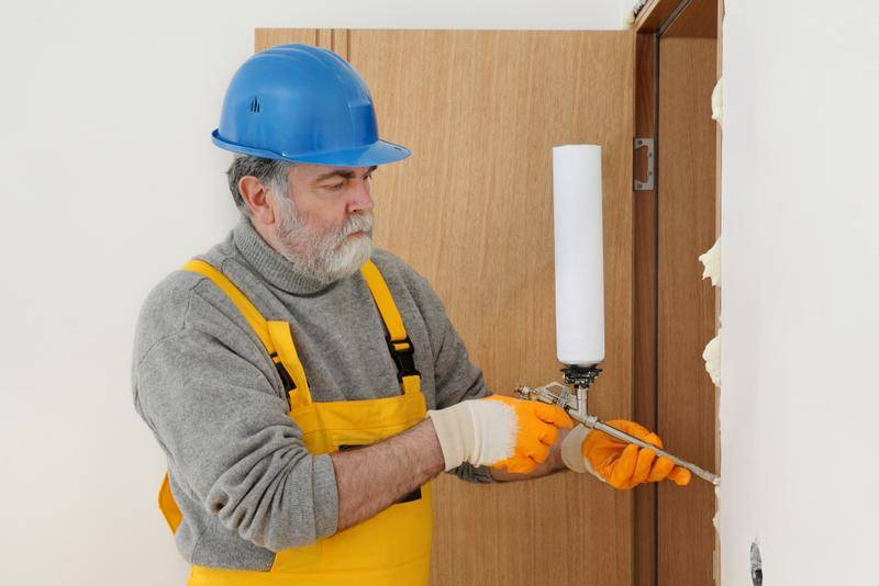 Worker installing wooden door, using polyurethane foam